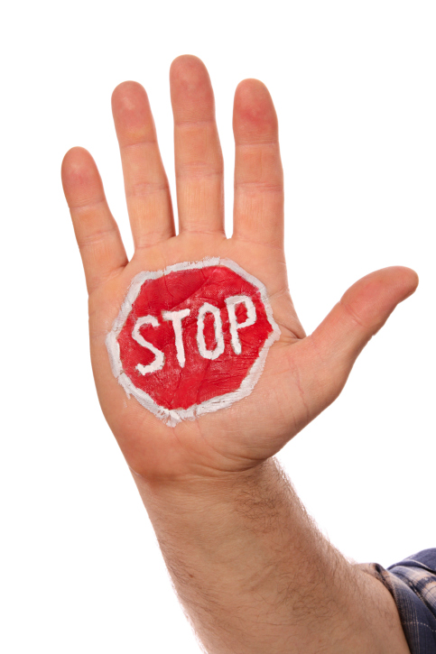 stop sign painted on the palm of a hand