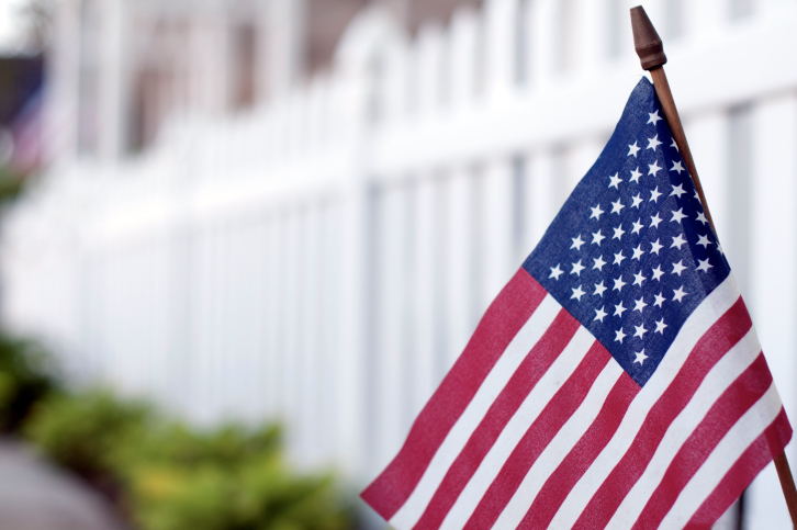 american flag in front of white picket fence