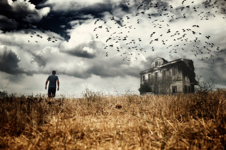 man walking n a field to an neglected house