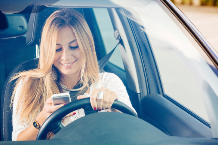 woman sending a text message while driving