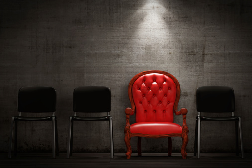 red chair standing out from crowd of black chairs