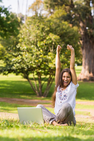 Excited woman outside on laptop